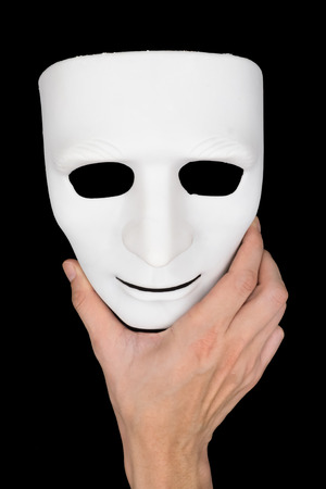 canvass: Hand holding white mask on black background.