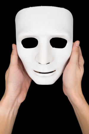canvass: Hands holding white mask on black background. Stock Photo