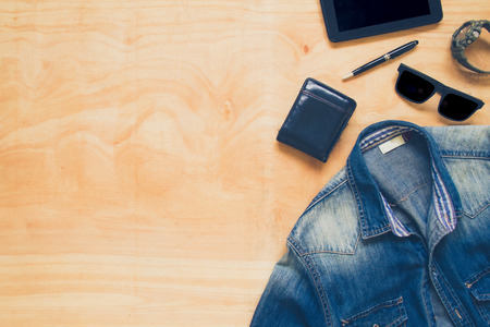 personal accessory: Top view of clothing and diverse personal accessory on the wooden table background.
