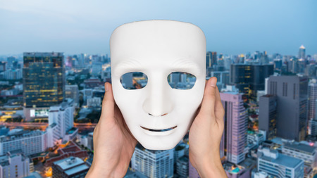 canvass: Hands holding white mask on blurred city landscape background.