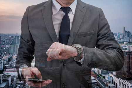 Double exposed of Businessman checking time on his wrist watch and holding mobile phone with cityscape. Stock Photo