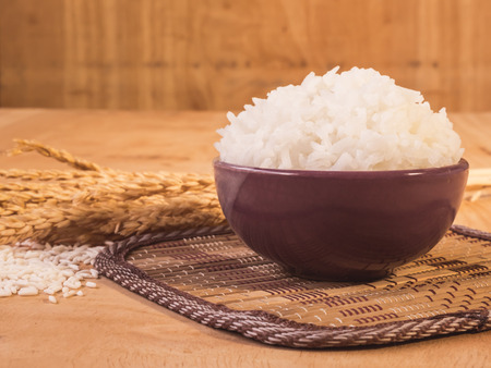 Cooked rice in bowl with raw rice grain and dry rice plant on  wooden table background.