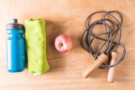 Top view of bottle with towel,apple and skipping rope on wooden table background, Fitness lifestyle concept