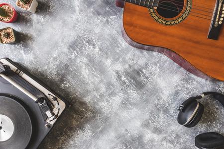 グランジ背景、テキストの空き領域にギター、ヘッドフォンとサボテンとヴィンテージのターン テーブルの上から見る