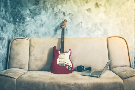 avocation: Electric guitar with laptop and headphone on a sofa. Vintage tone. Stock Photo