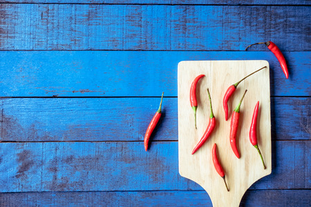 hottest: Top view of Red hot chilli peppers on tray over blue wooden table background, Free space for text