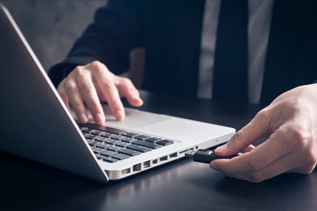 Close up of Businessman using flash drive connect to laptop on the office desk. Foto de archivo
