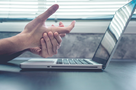 Close up hand pain from working on laptop, Office syndrome concept. Stock Photo - 67090891