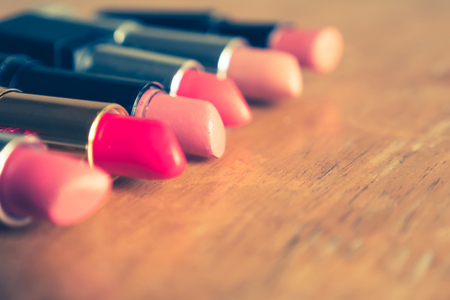 Colorful lipsticks on the wooden table. Makeup and Beauty concept. Selective focus