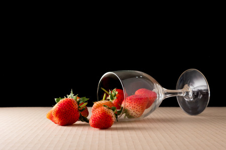 Strawberries with glass of wine on black background.