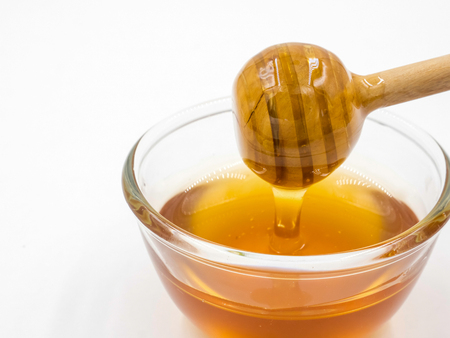 Honey with wood stick on white background.