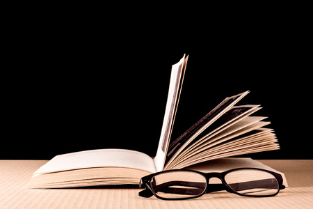Book and eyeglasses on wooden table, Black background Stockfoto