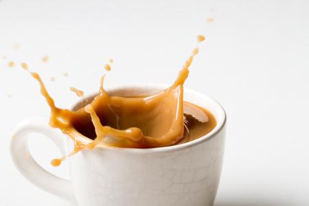 Cup of splashing coffee on white background Foto de archivo