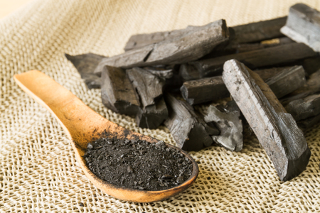 Charcoal and charcoal powder on wooden spoon. Selective focus Stock Photo - 74349342