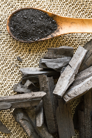 Charcoal and charcoal powder on wooden spoon. Selective focus Stock Photo