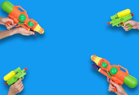 파란색 배경에 총 물 장난감을 들고 손입니다.