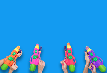 Hands holding gun water toy on blue background.