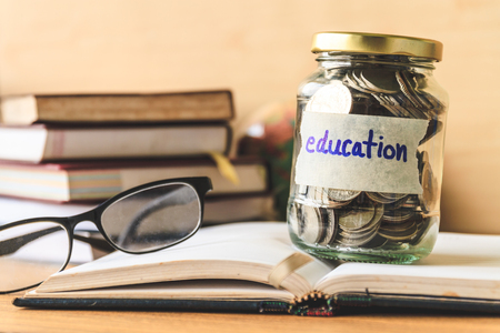 Coins in glass jar with education label, books,glasses and globe on wooden table. Financial concept.