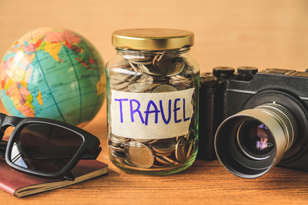 Coins in glass jar with accessories of traveler on wooden table. Saving money for travel concept