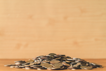Pile of coins on a wooden table. Financial Concept. Selective focus. Free space for text