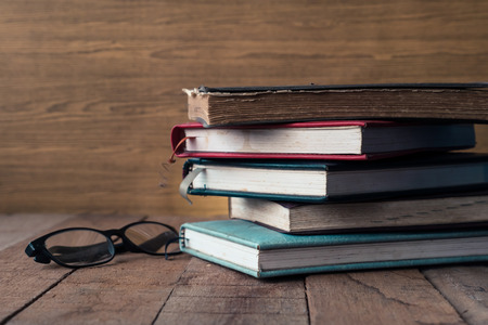 untidiness: Old hardback books with glasses on wooden table. Stock Photo
