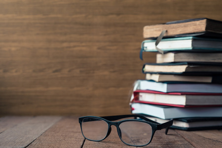 untidiness: Glasses with hardback books on wooden table. Free space for text. Selective focus
