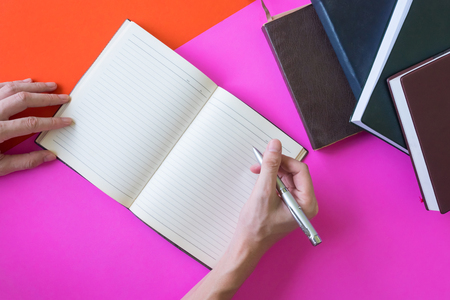 Male hands writing on notebook, hardback book on colorful background
