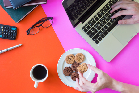 Male hands holding cookies and using laptop, coffee cup and office supplies on colorful background.
