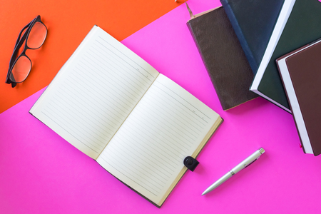 Open blank notebook with pen, glasses and hardback books on colorful background.