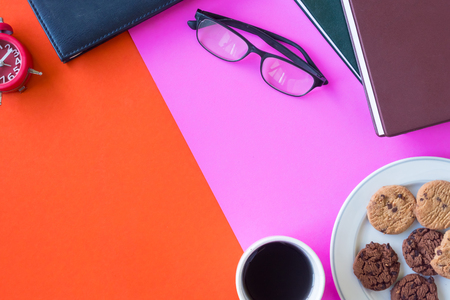 Books, glasses, clock, cookies and coffee cup on colorful background. Free space for text
