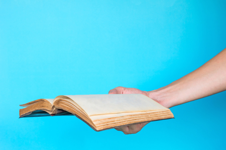 Male hand holding blank notebook on blue background. Free space for text