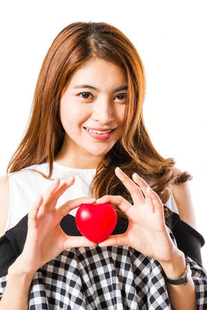 Beautiful happy woman holding red heart on a white background.