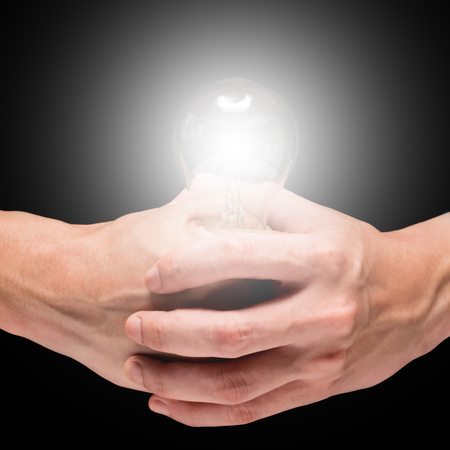 Male hands holding light bulb on a black background.