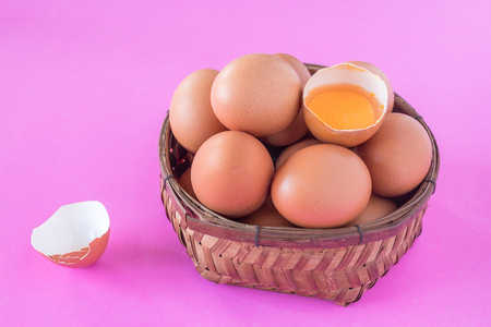 Eggs in wooden basket on a pink background.