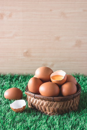 Eggs in wooden basket on green grass. Free space for text Stock Photo