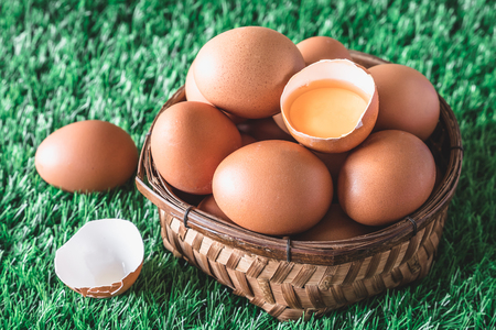 Eggs in wooden basket on green grass. Selective focus