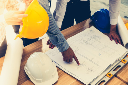 expertise: Team of engineers discussing architecture plan sketch at the construction site. Vintage tone Stock Photo