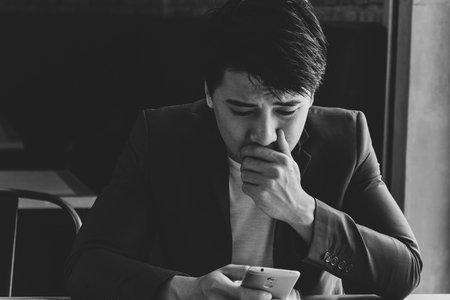 Desperate sad young businessman looking at bad text message on his mobile phone. Black and white tone