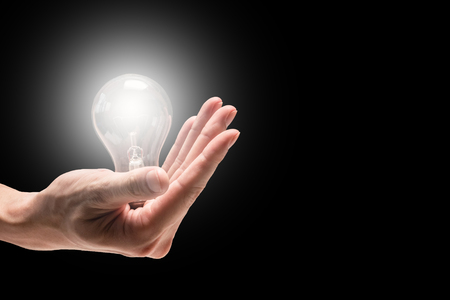 Male hand holding light bulb on a black background. Free space for text