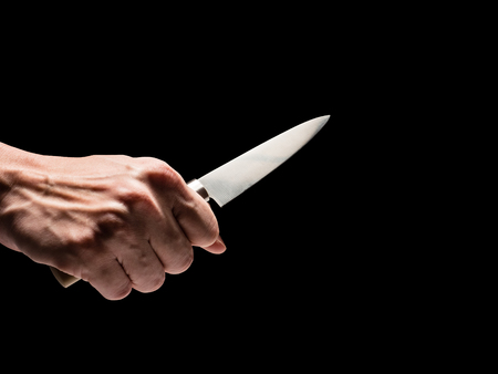 Male hand holding knife on black background.