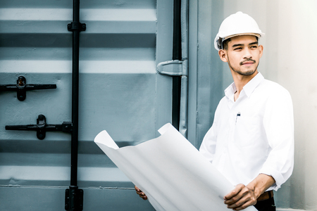 Civil engineer holding blueprint at the construction site. Stock Photo