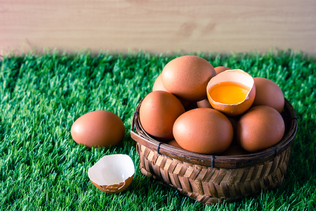 Eggs in wooden basket on green grass.