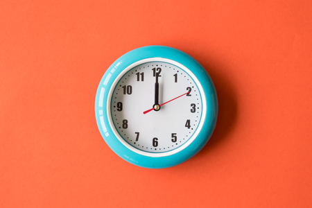 Blue wall clock on orange background, twelve oclock