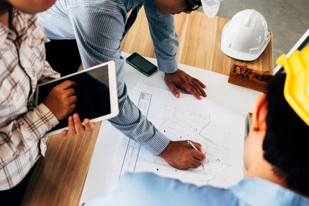 Team van ingenieurs die de schets van het architectuurplan bespreken bij de bouwwerf.