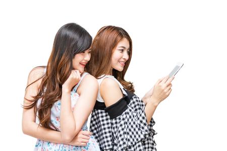 使用して 2 つの美しい幸せな女性は、白の背景にタブレットします。