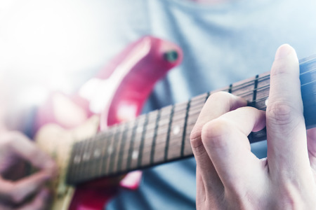Close up of Male hands playing electric guitar, Flare from the sunlight, Selective focus Stock Photo