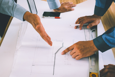 Team of engineers discussing architecture plan sketch at the construction site. Stock Photo
