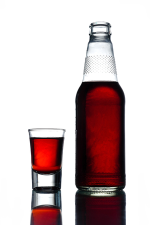 Bottle of alcohol with shot on a white background.