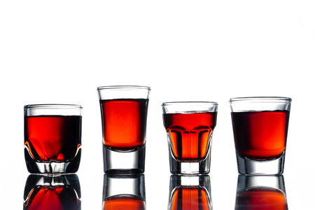 Collage of glasses with alcohol on a white background.