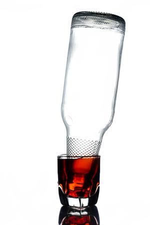 白い背景の空瓶が付いているアルコールのガラス。 写真素材